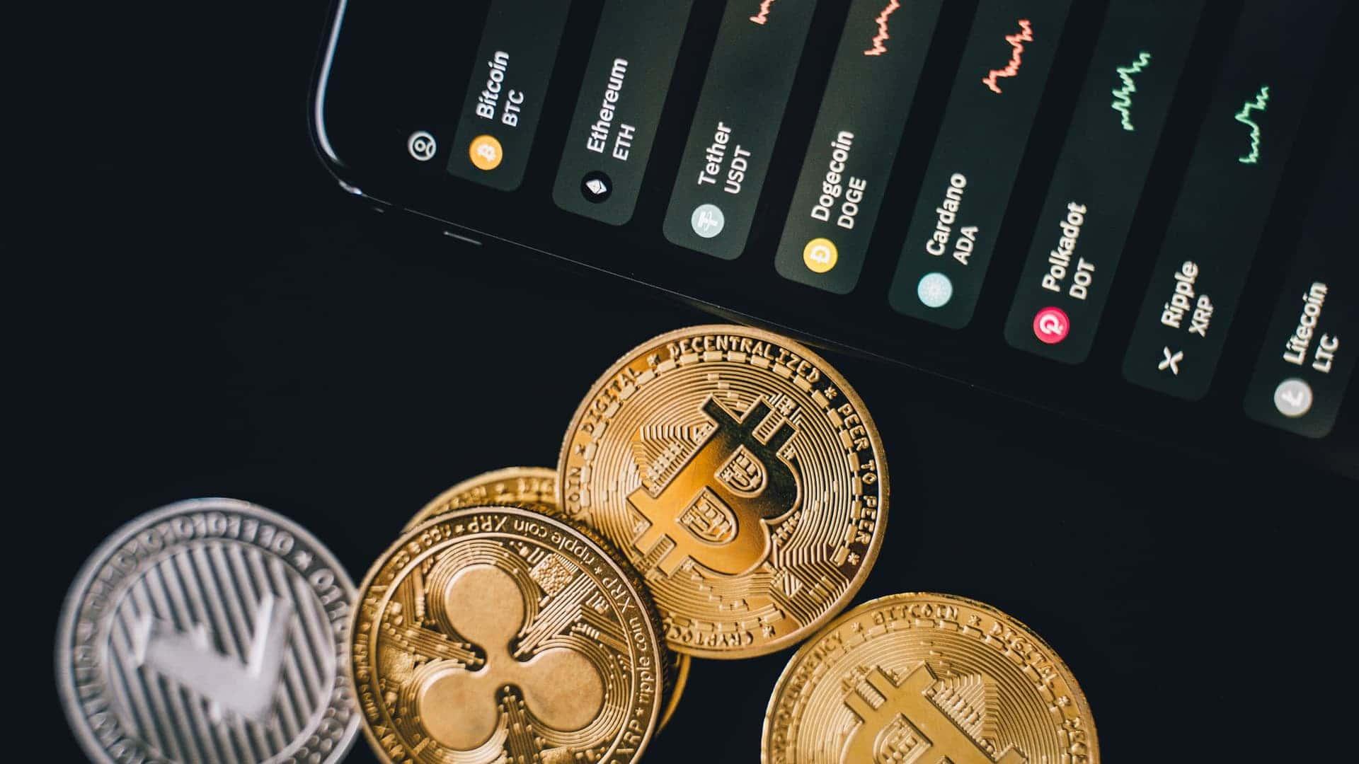 Gruppo di monete oro e argento vicino a uno schermo del telefono
