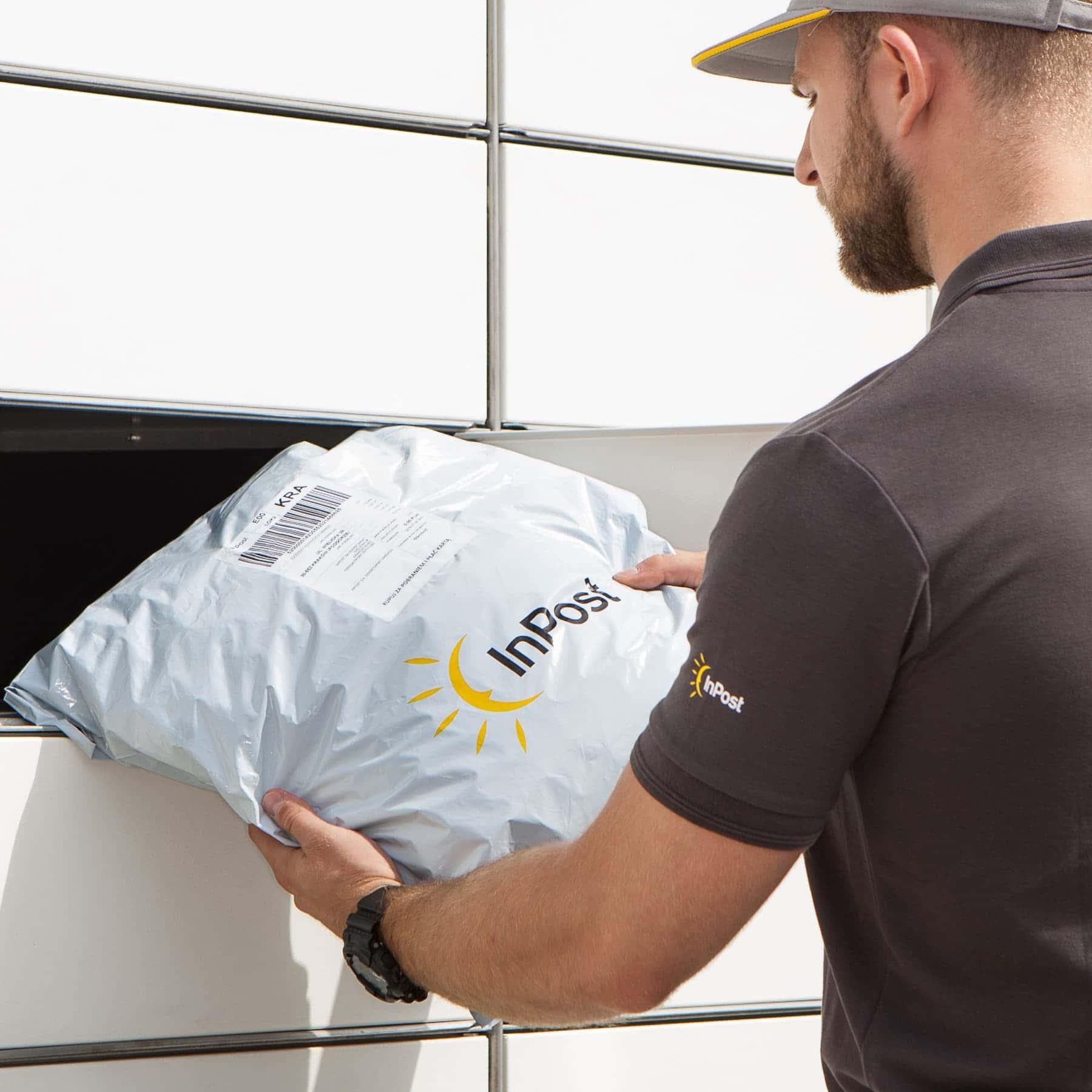Corriere consegna pacco all'interno di un locker InPost