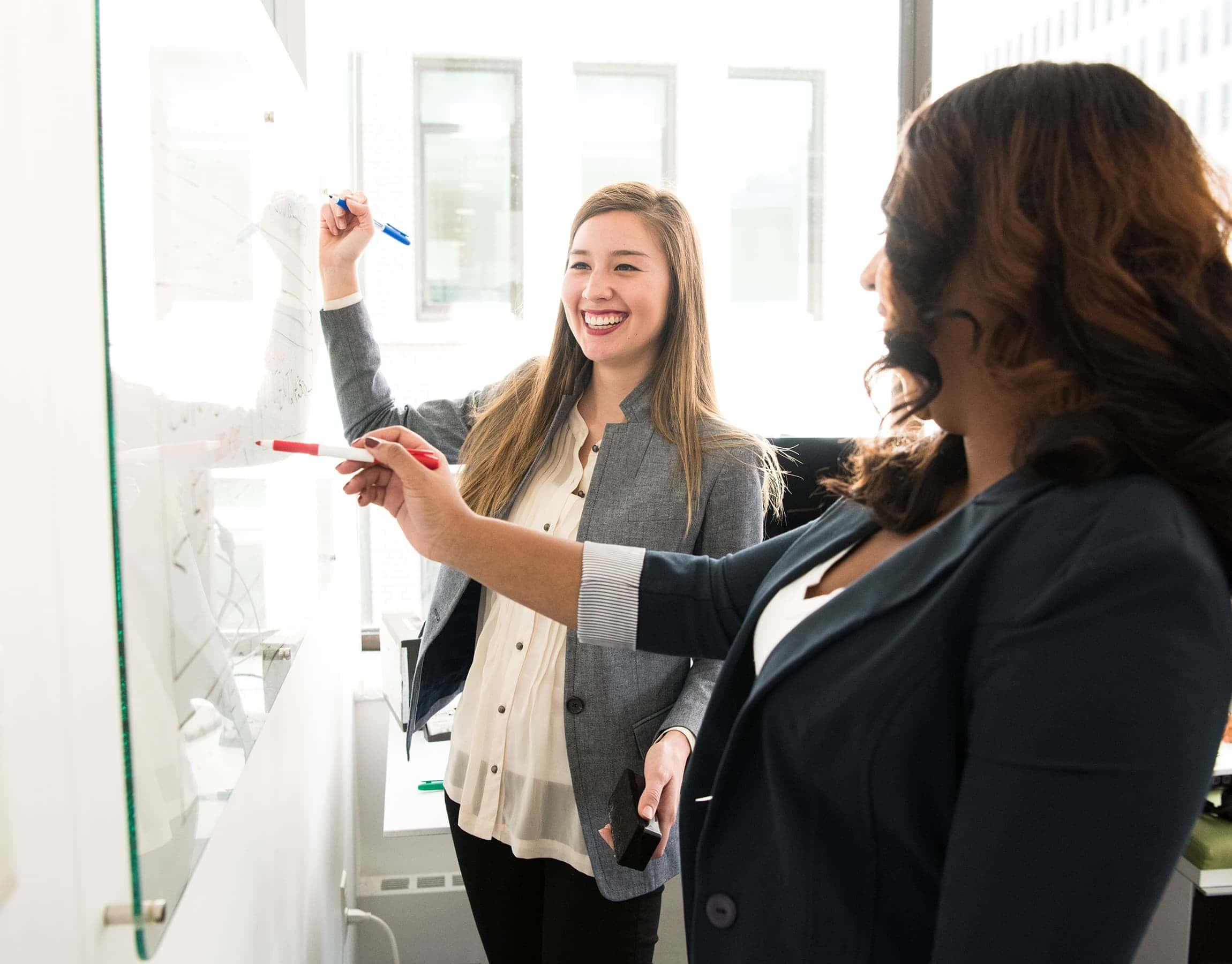 Due donne scrivono appunti alla lavagna dell'ufficio