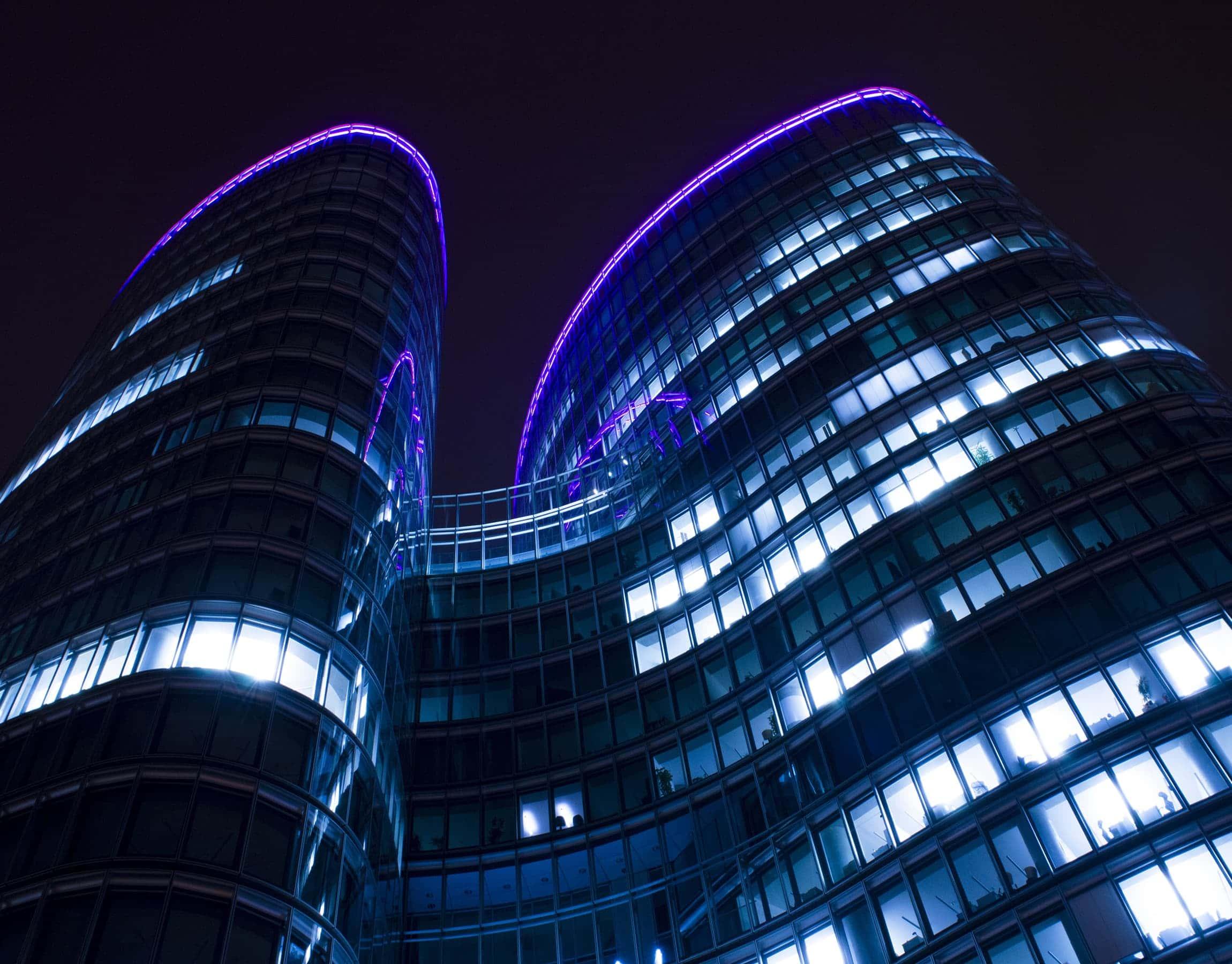 Palazzo moderno illuminato di notte con neon viola sul tetto